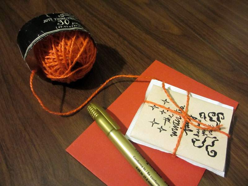 Example of a completed card packaged with the teabag and tied with twine, on top of persimmon coloured envelope with metallic gold marker